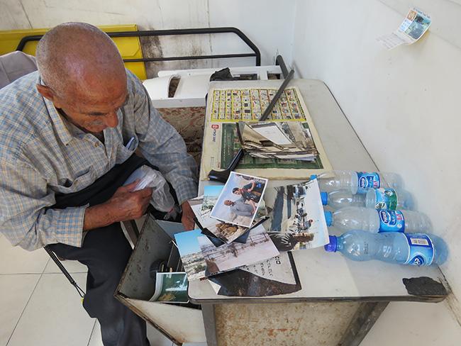 """עבד סייאד במשרדו הזעיר שבלב חלקת """"קהילת ירושלים"""" מוציא עבד מסמכים ותמונות"""